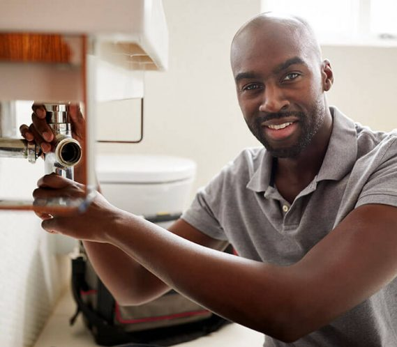 male plumber working on sink happy after getting great plumber digital marketing